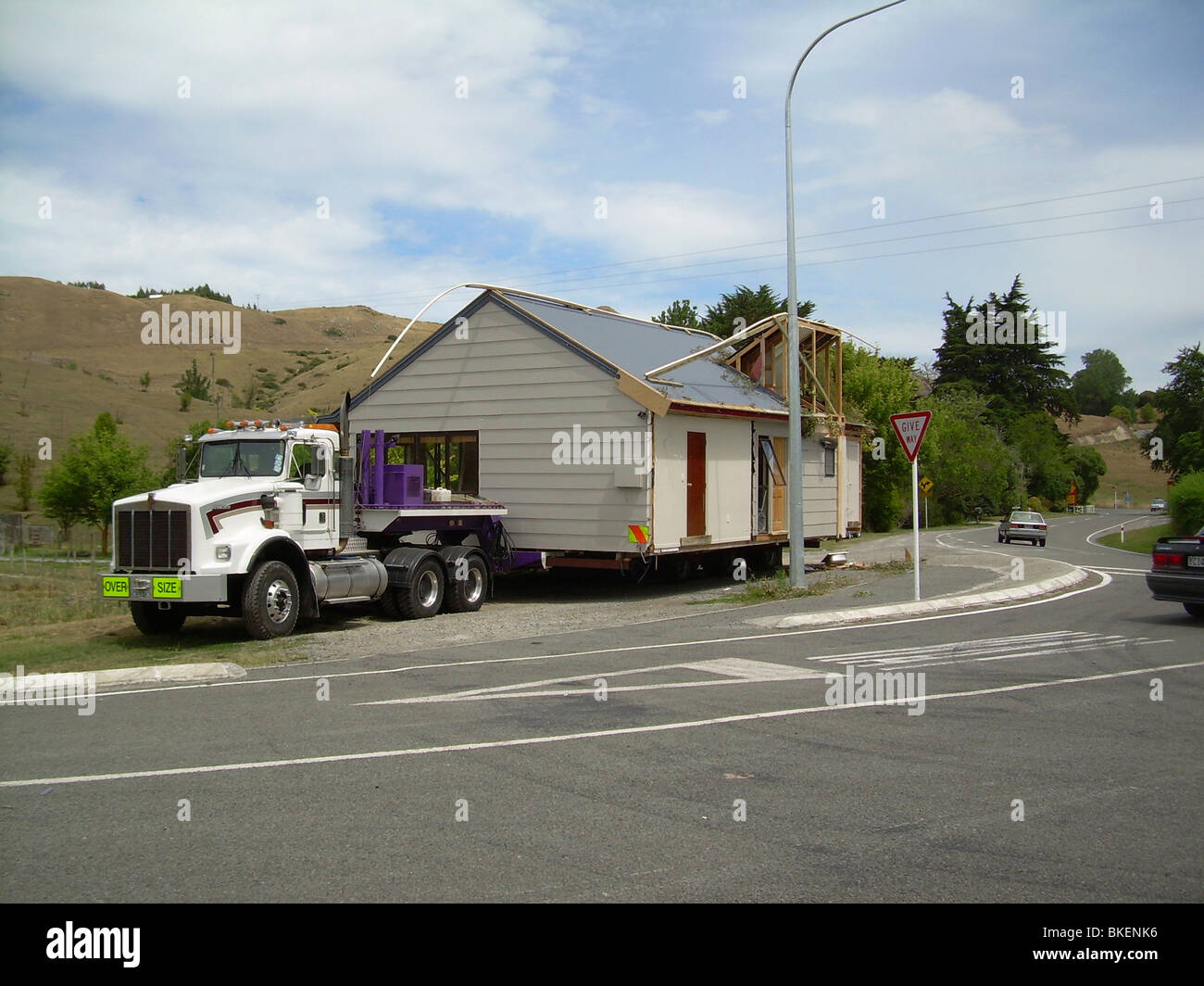 house moving truck with house on parked on side of road Stock Photo