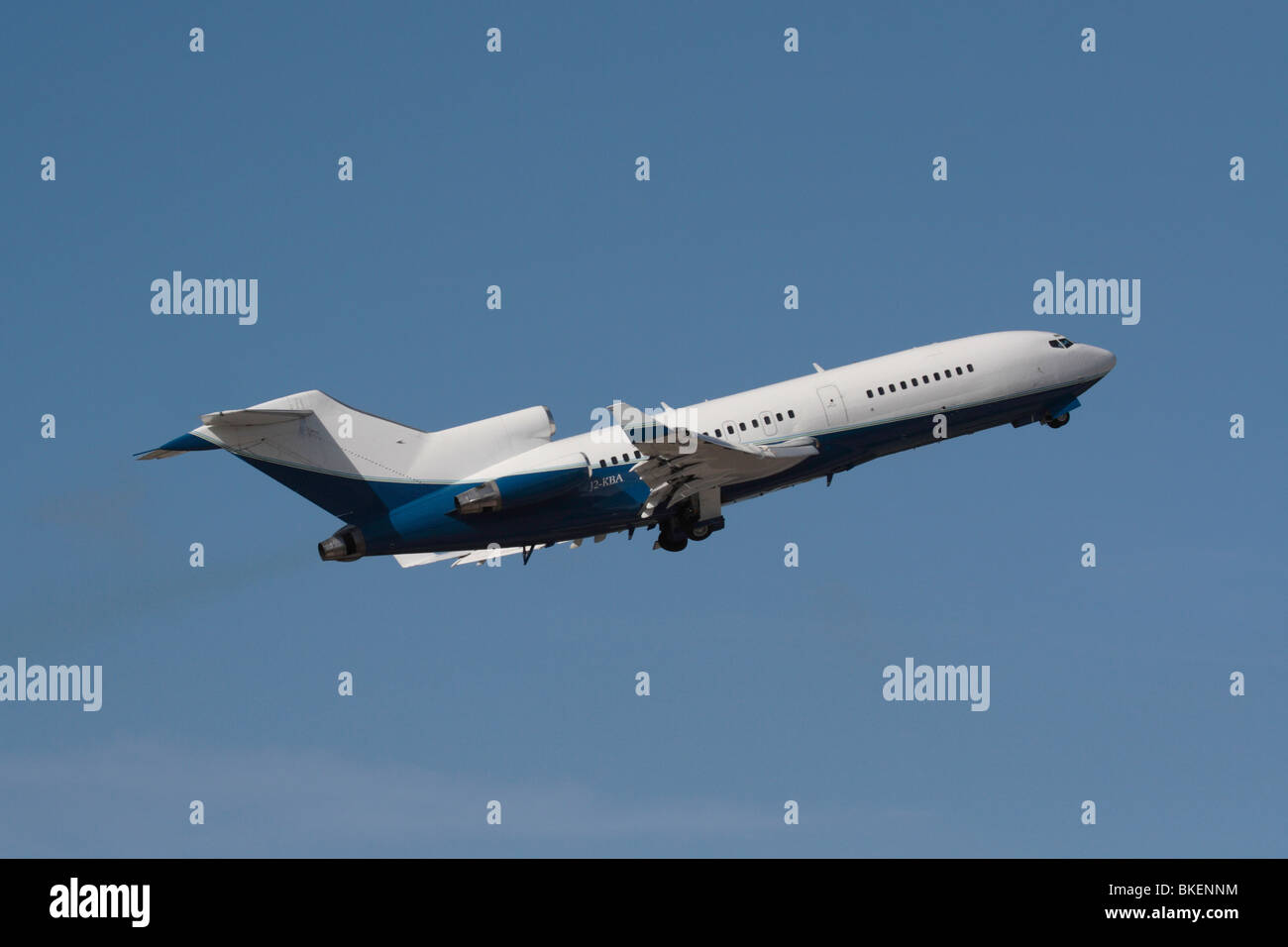 Boeing 727 commercial passenger jet plane flying on takeoff against a blue sky - Stock Image