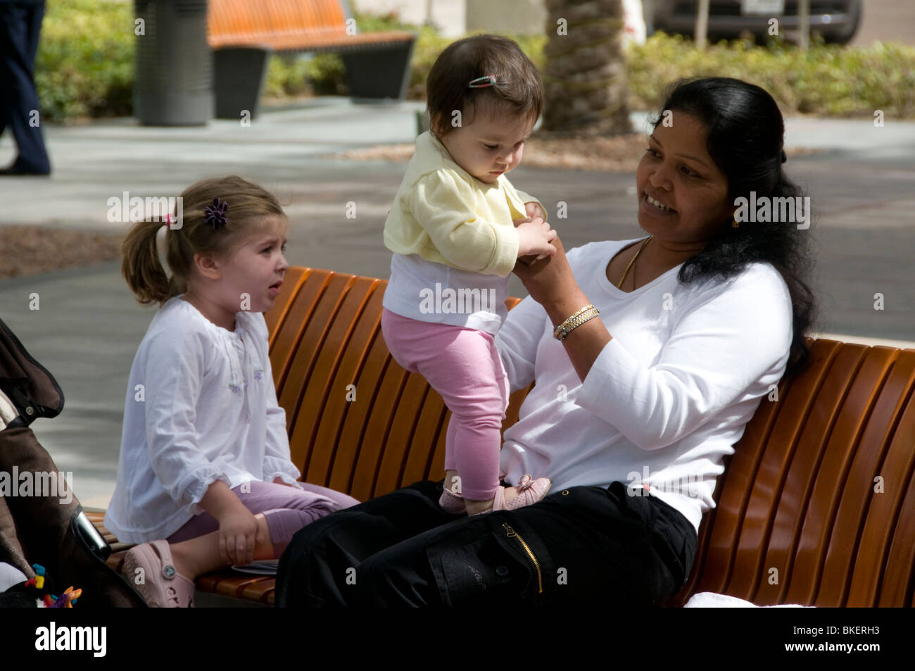 A nanny playing with children - Stock Image