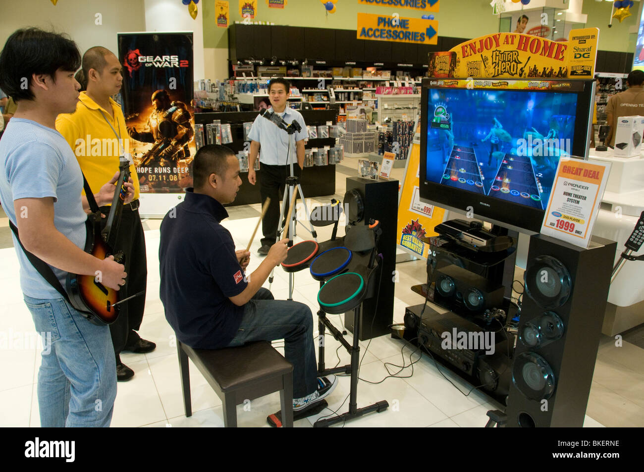 People playing Guitar Hero in a shop - Stock Image