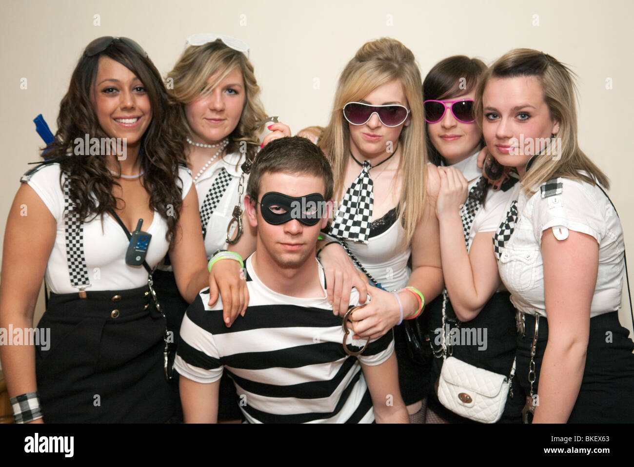 Group of teenagers teens teenage boys and girls dressed up to go out to a  fancy dress party, UK