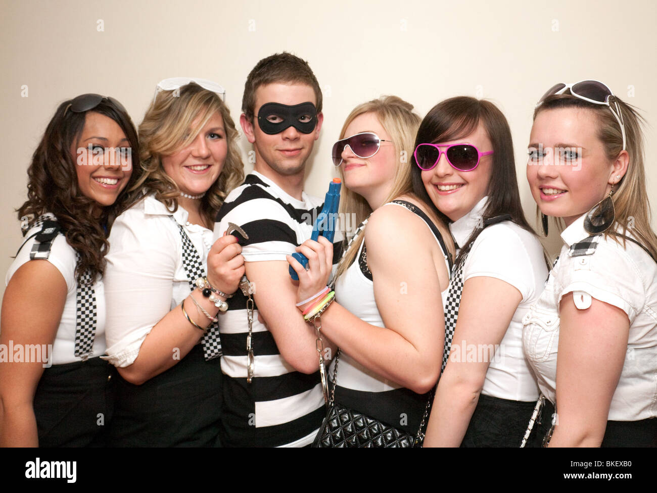 Teenagers dressed up to go to a cops and robbers fancy dress party, UK - Stock Image