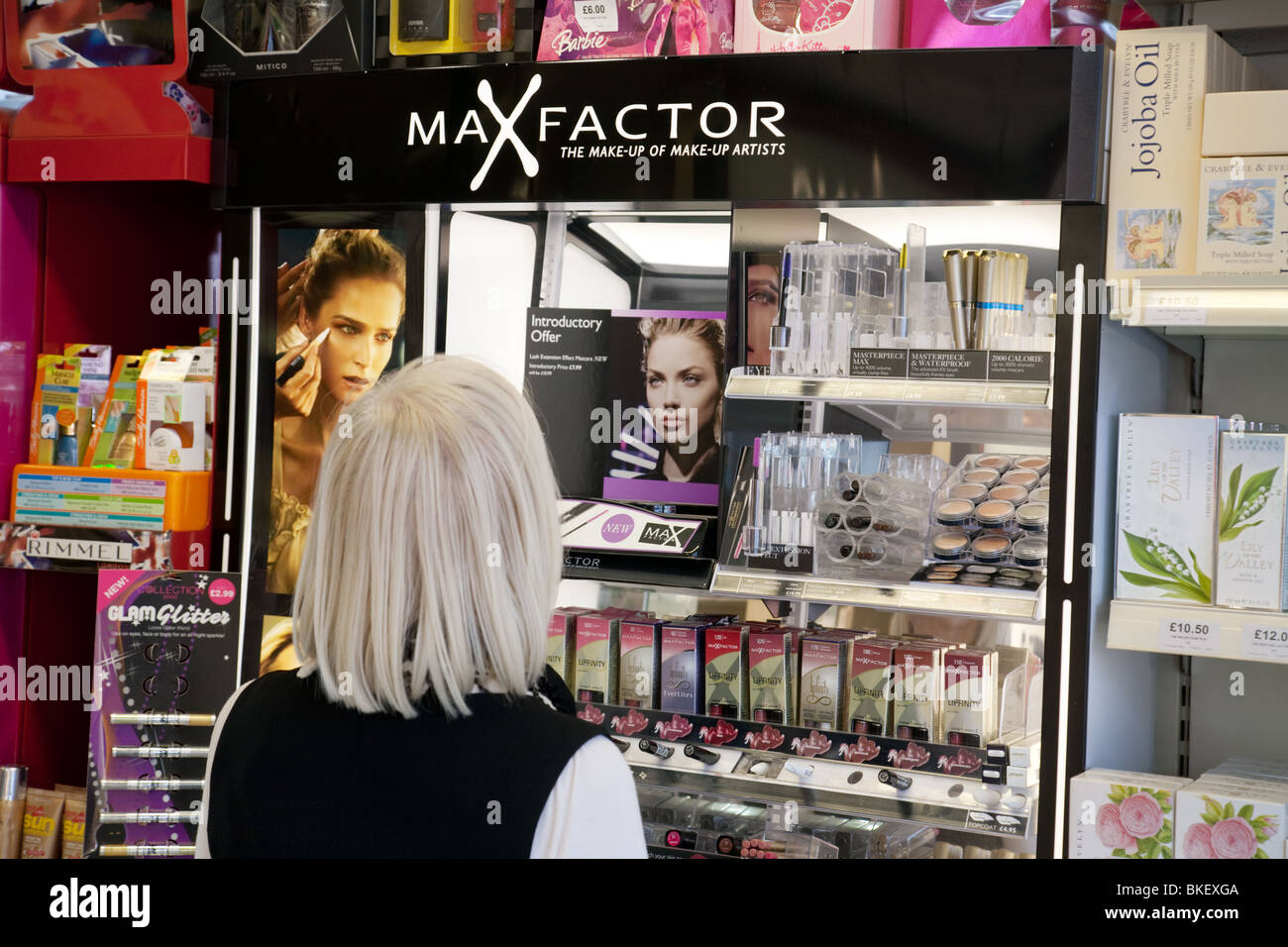 A woman looking at Max Factor cosmetics in a shop, Kent, UK - Stock Image