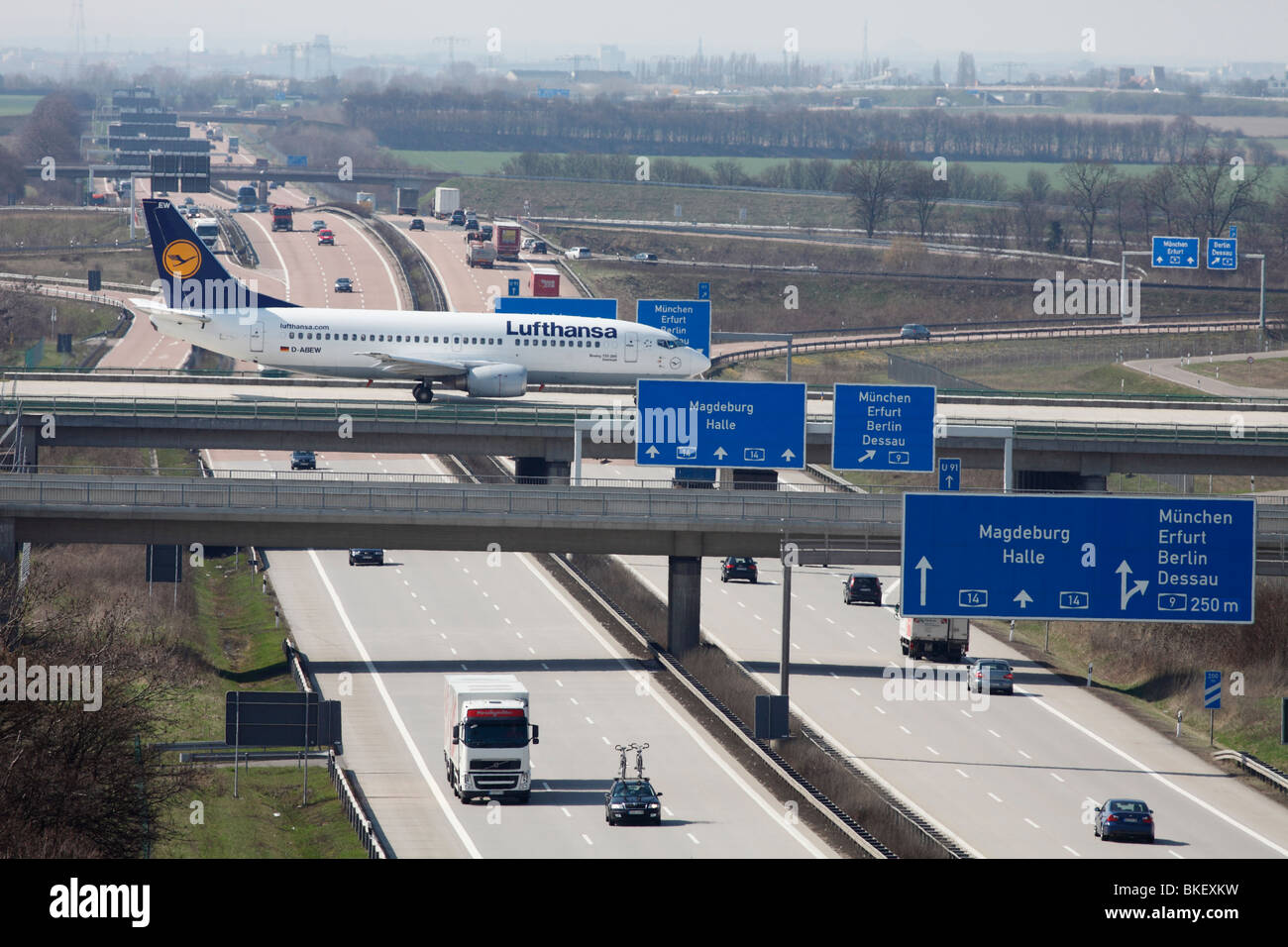 airplane of Lufthansa on motorway bridge at the airport Leipzig-Halle in Germany - Stock Image