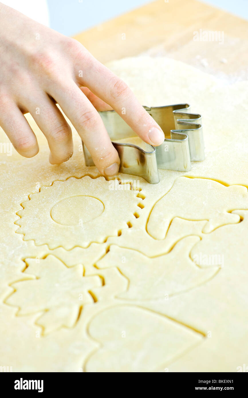 Cutting cookie shapes in rolled dough with cutter - Stock Image