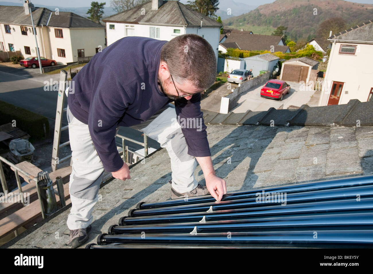 A householder fitting a solar water heating panel to his house roof in Ambleside cumbria UK - Stock Image