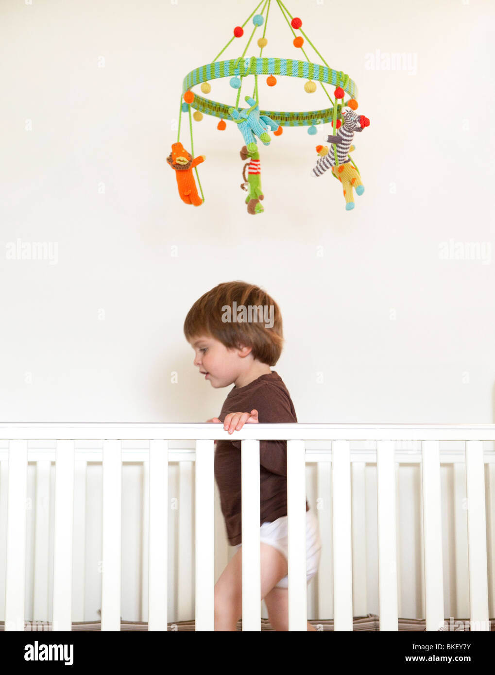 Baby standing in crib beneath mobile - Stock Image
