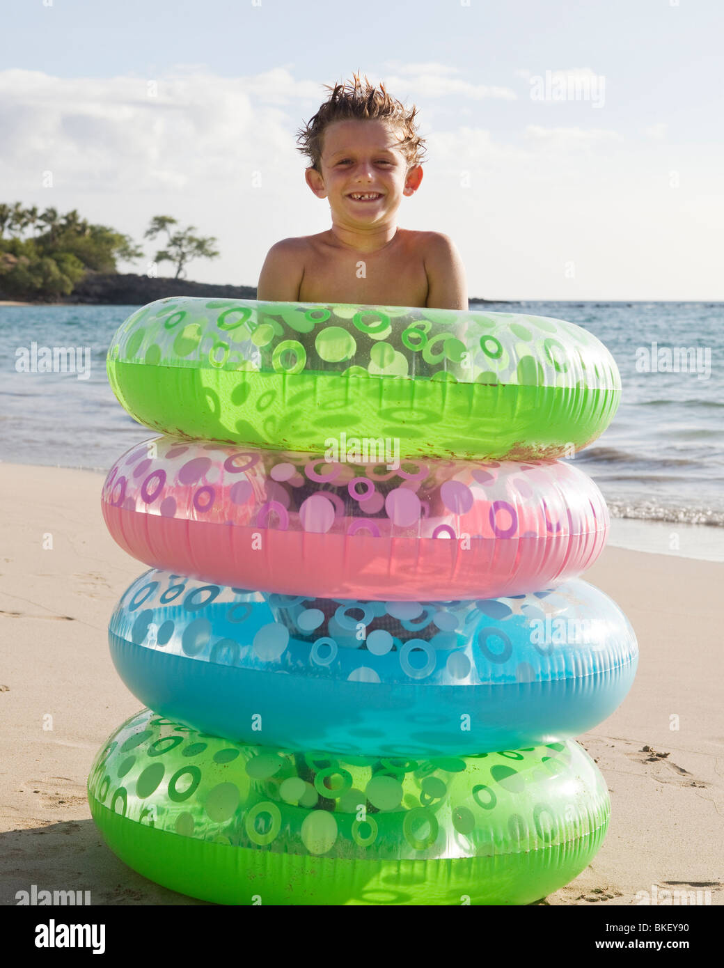 Boy surronded by stack of colorful inner tubes - Stock Image