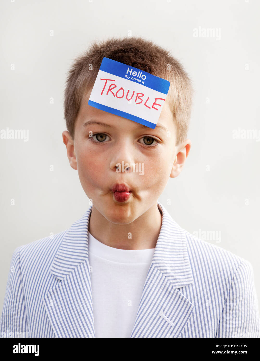 Trouble name tag on boys forehead - Stock Image