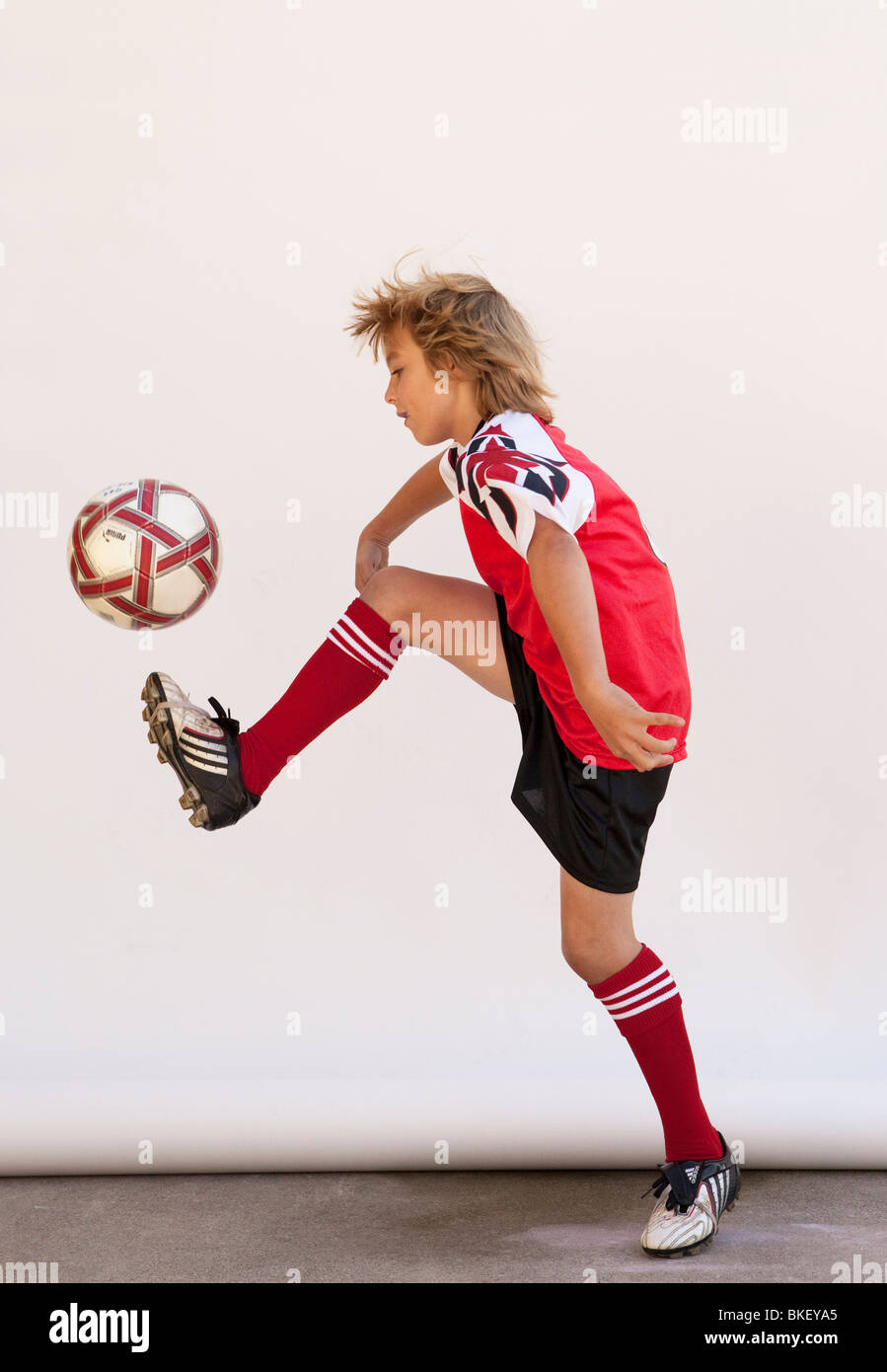 Boy with soccer ball in soccer uniform - Stock Image