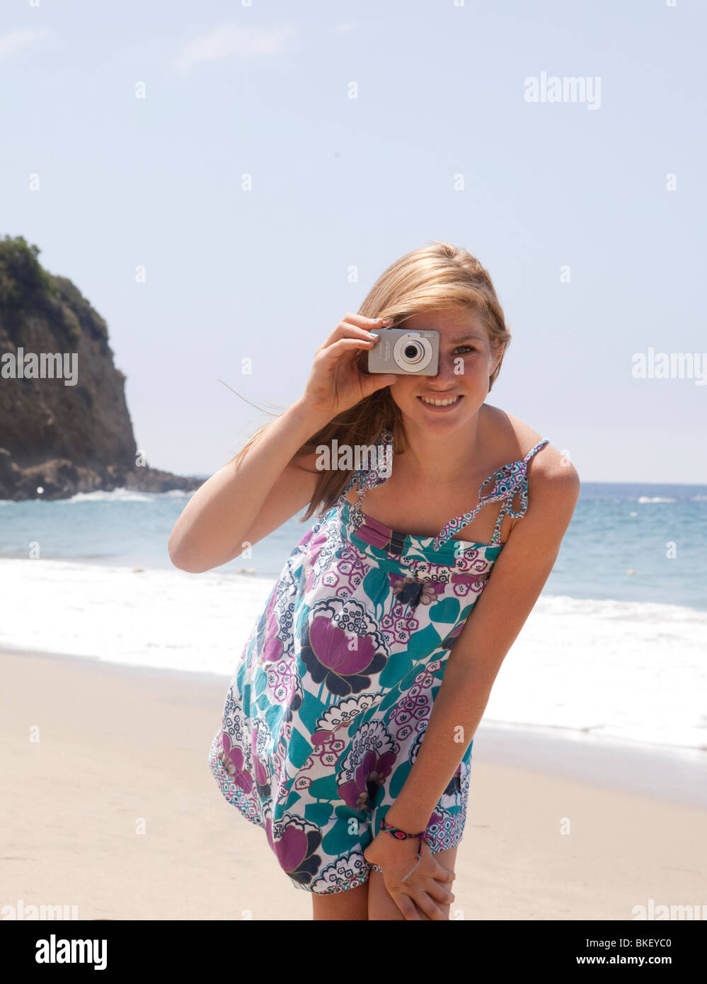 Teenage girl taking picture at beach - Stock Image