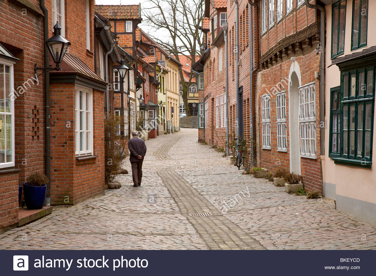 Old man walking down a cobbled street in Lüneburg old town. Lower Saxony, Germany. - Stock Image