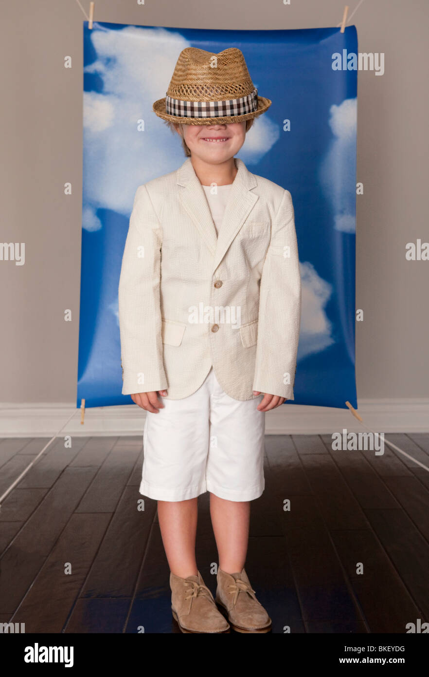 Dressed up boy in front of blue sky back drop - Stock Image