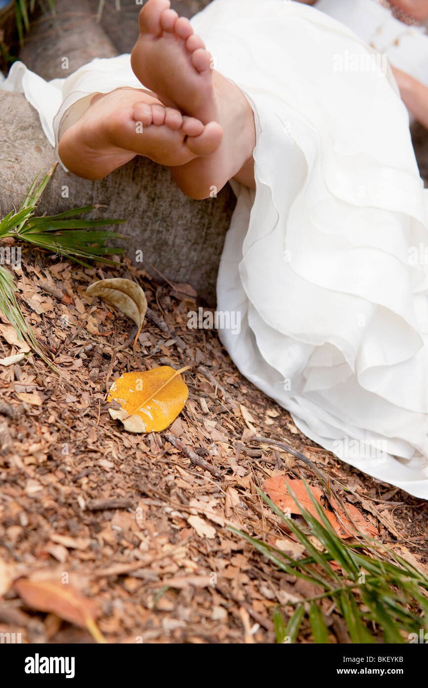 earthy green bride, barefoot, dirty feet, relax, bride reclining on the ground under tree, roots, earth, leaves, - Stock Image