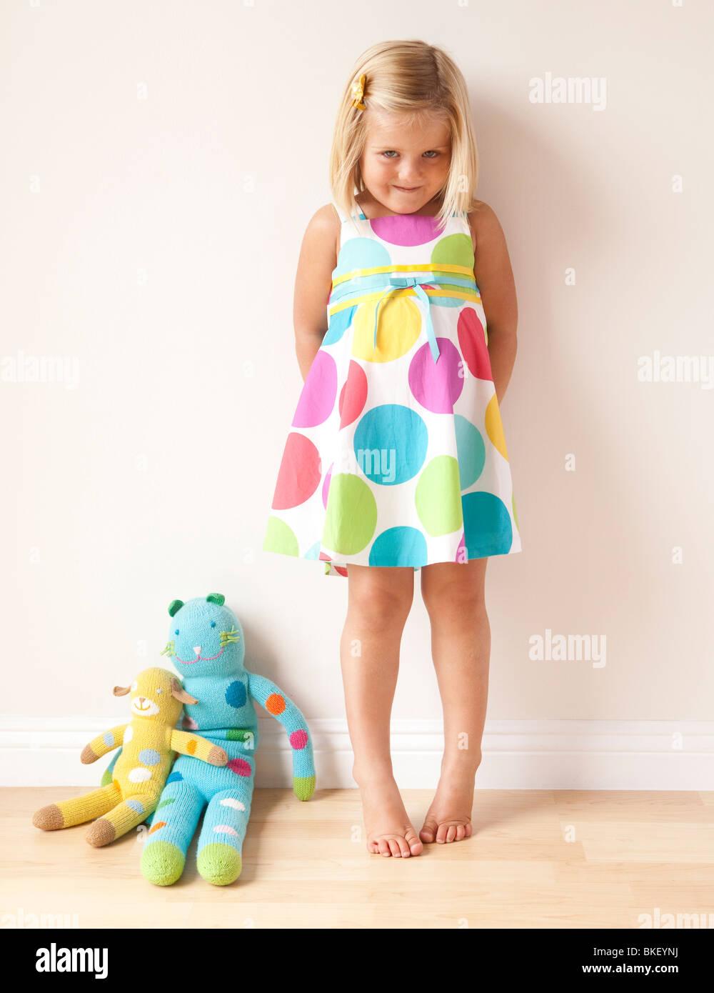 Bashful girl in polka dot dress - Stock Image