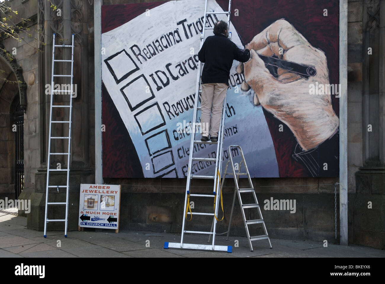 A mural being painted on a church wall commenting on the issues of the upcoming election in the United Kingdom. - Stock Image