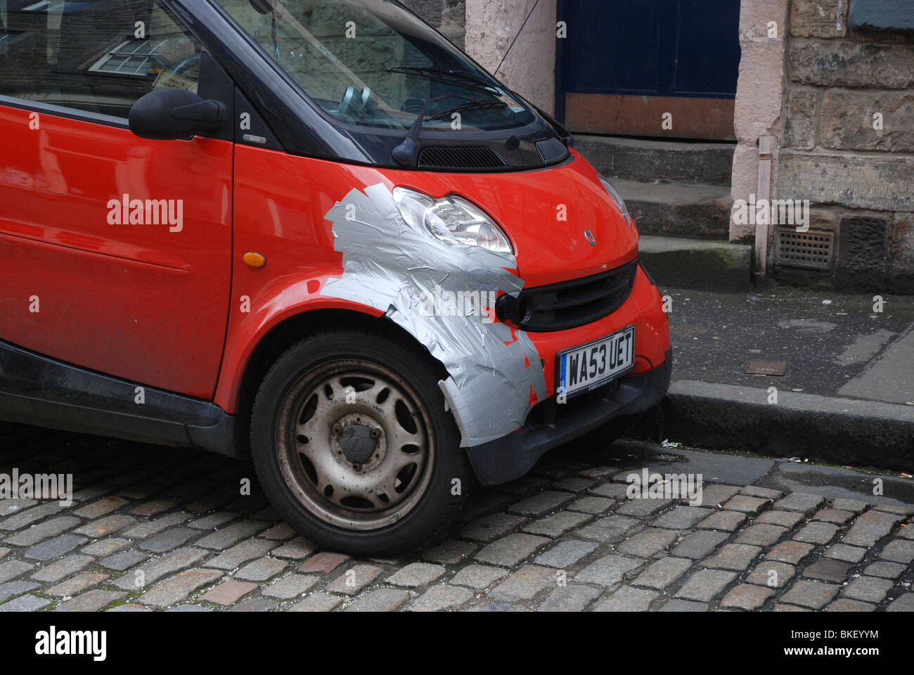 Smart car parked on a cobbled street with some damage temporarily repaired with silver tape. - Stock Image