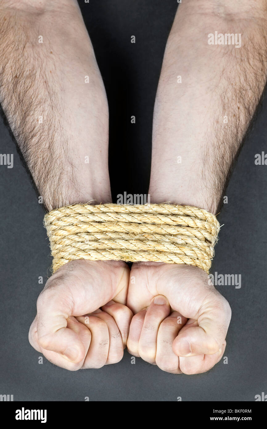 Male hands tied up with strong rope - Stock Image