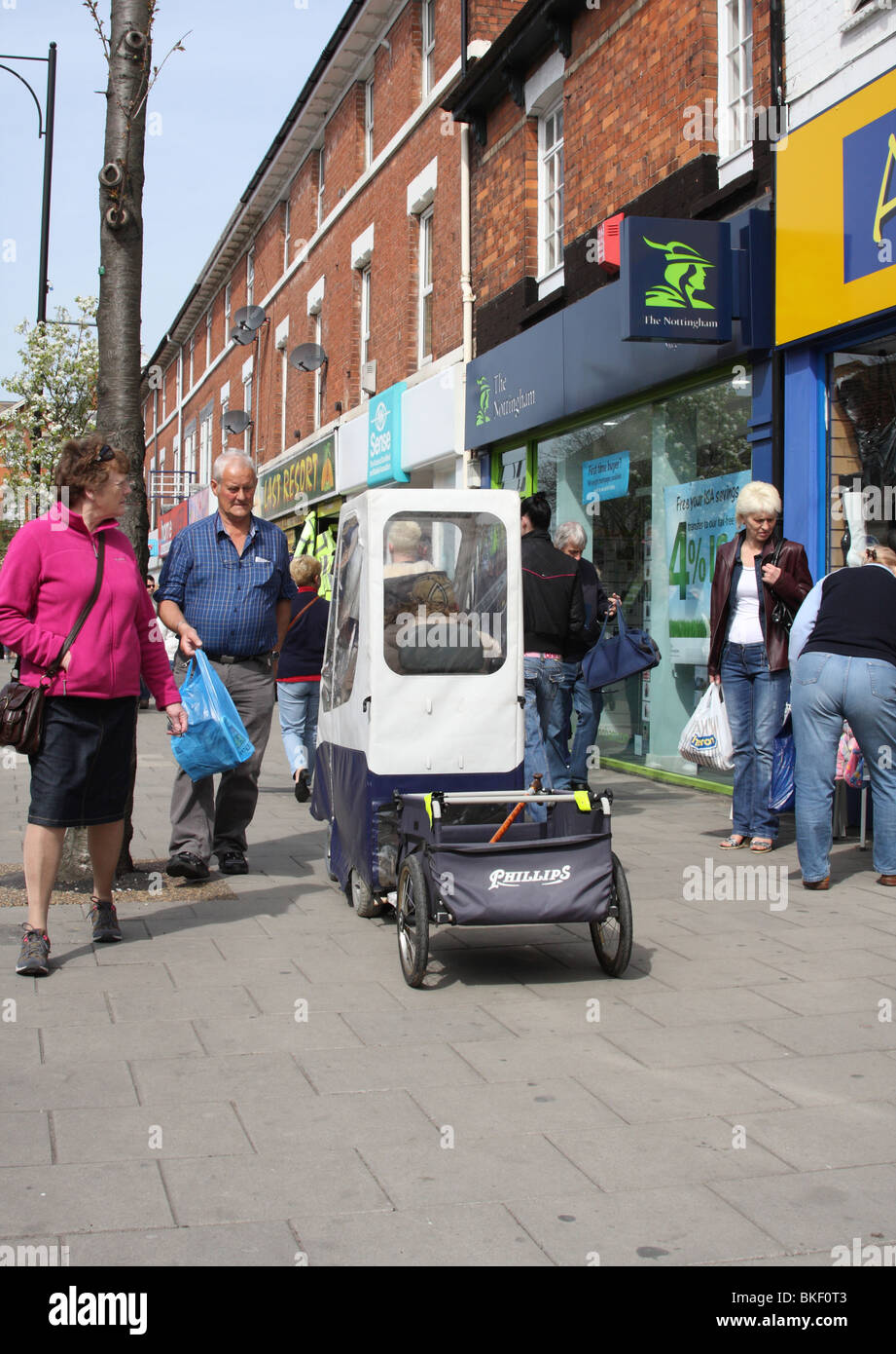 A mobility scooter on a busy street in the U.K. - Stock Image