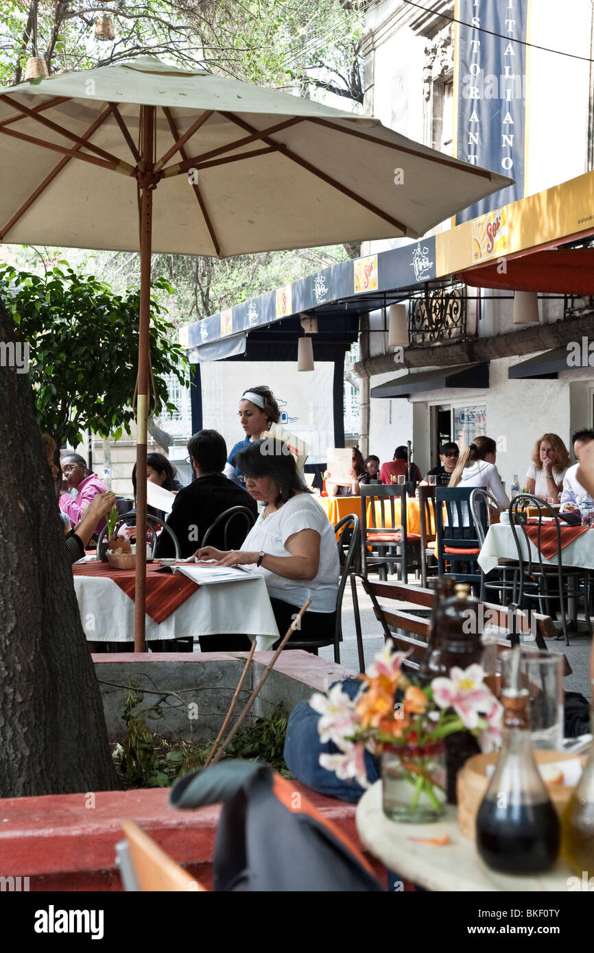 outdoor diners enjoy spring evening & bustling congenial sidewalk cafe scene Plaza Luis Cabrera in Roma district - Stock Image