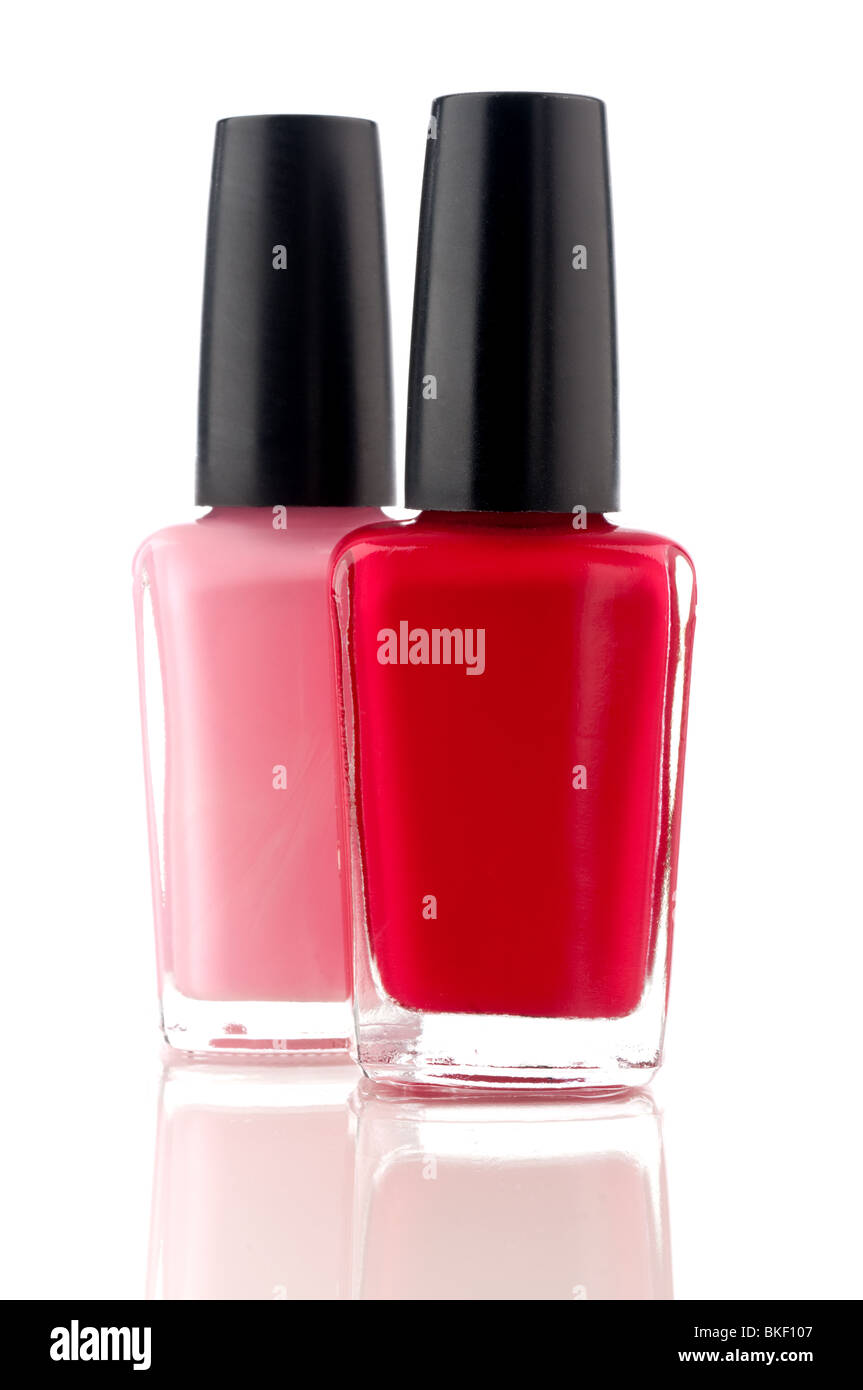 vertical image of red and pink nail polish on a white reflective ...