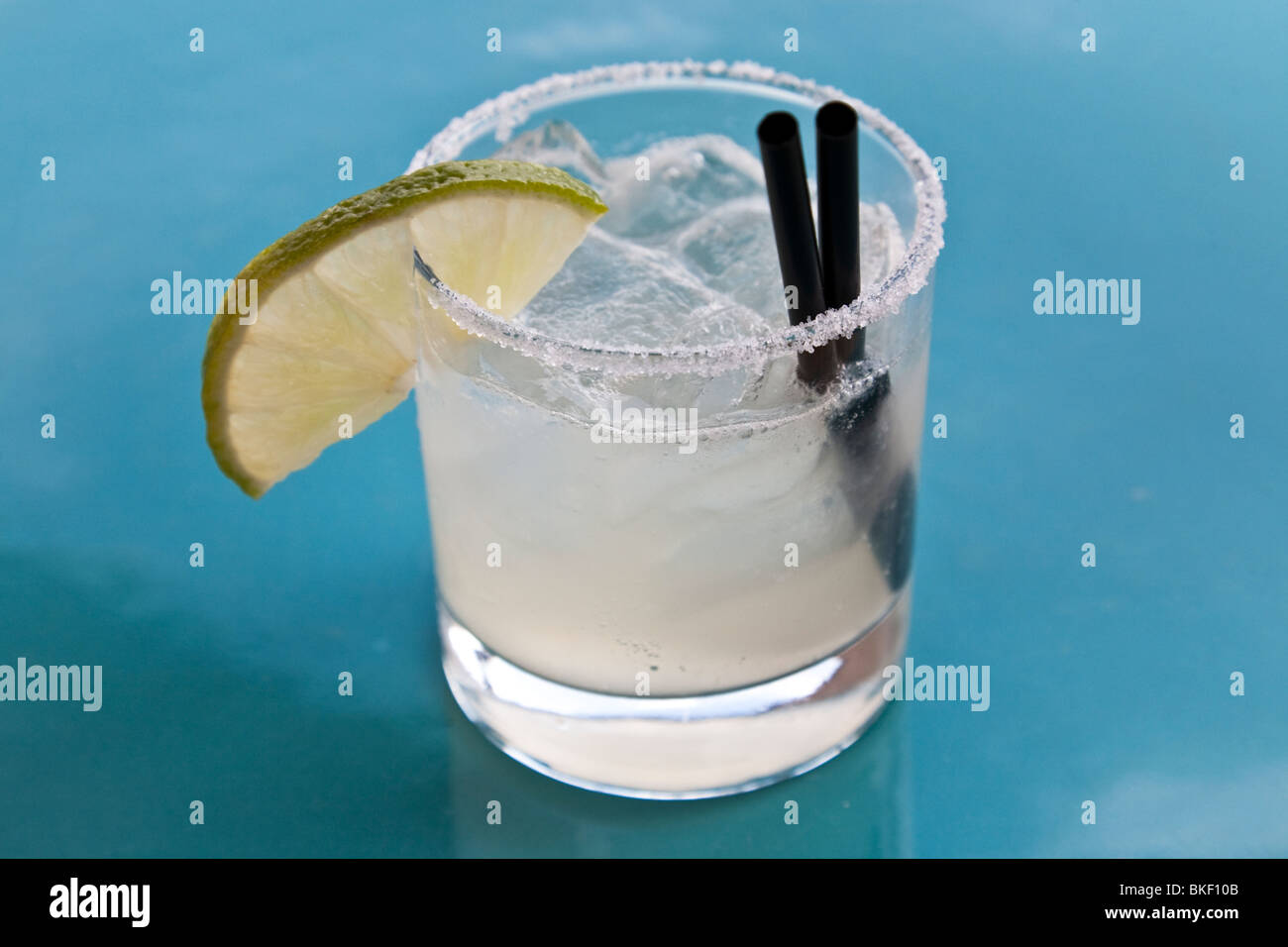 perfect classic Margarita with lime wedge & ice served in clear tumbler on blue table top at a rooftop bar in - Stock Image