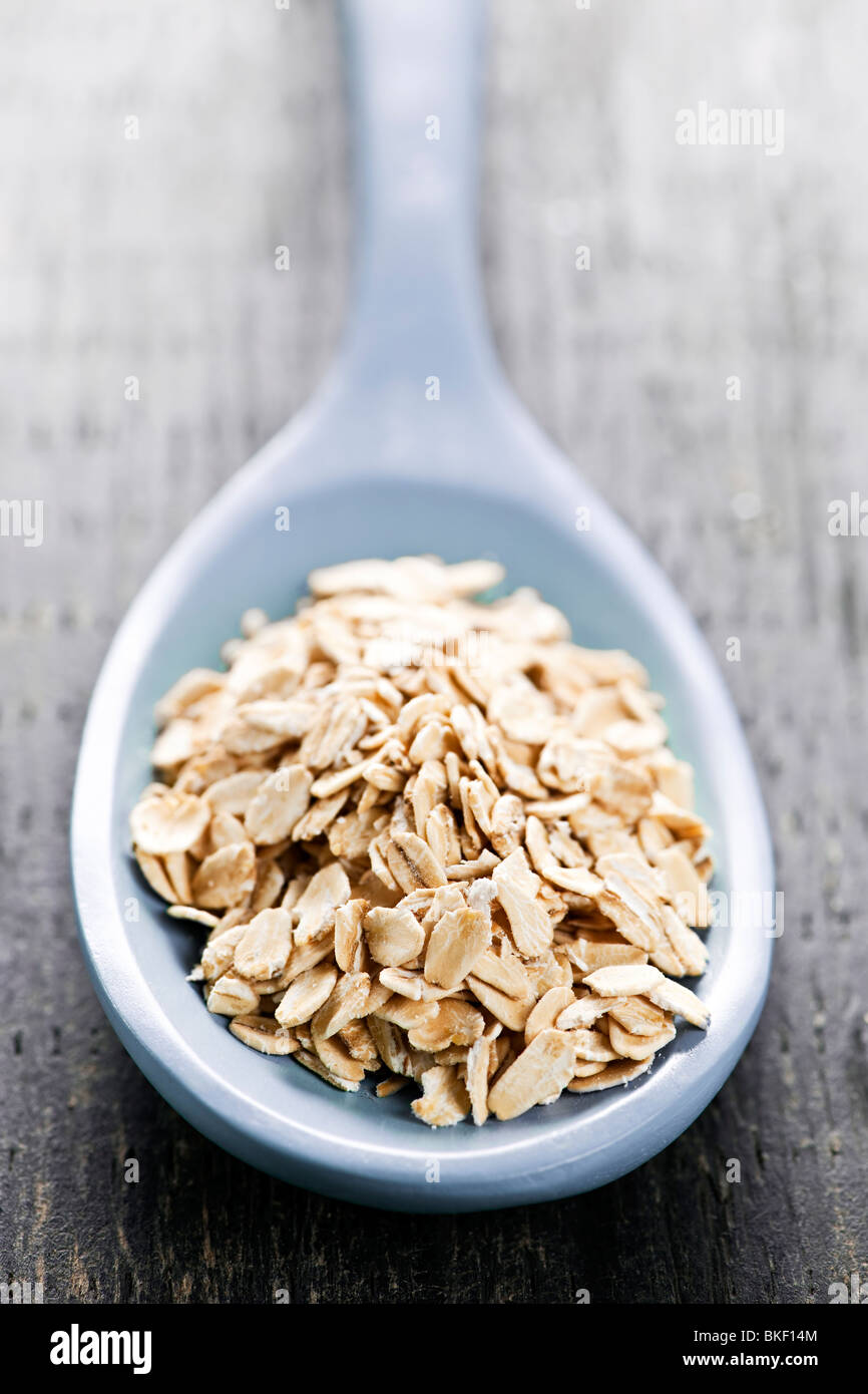 Nutritious rolled oats heaped on a spoon - Stock Image