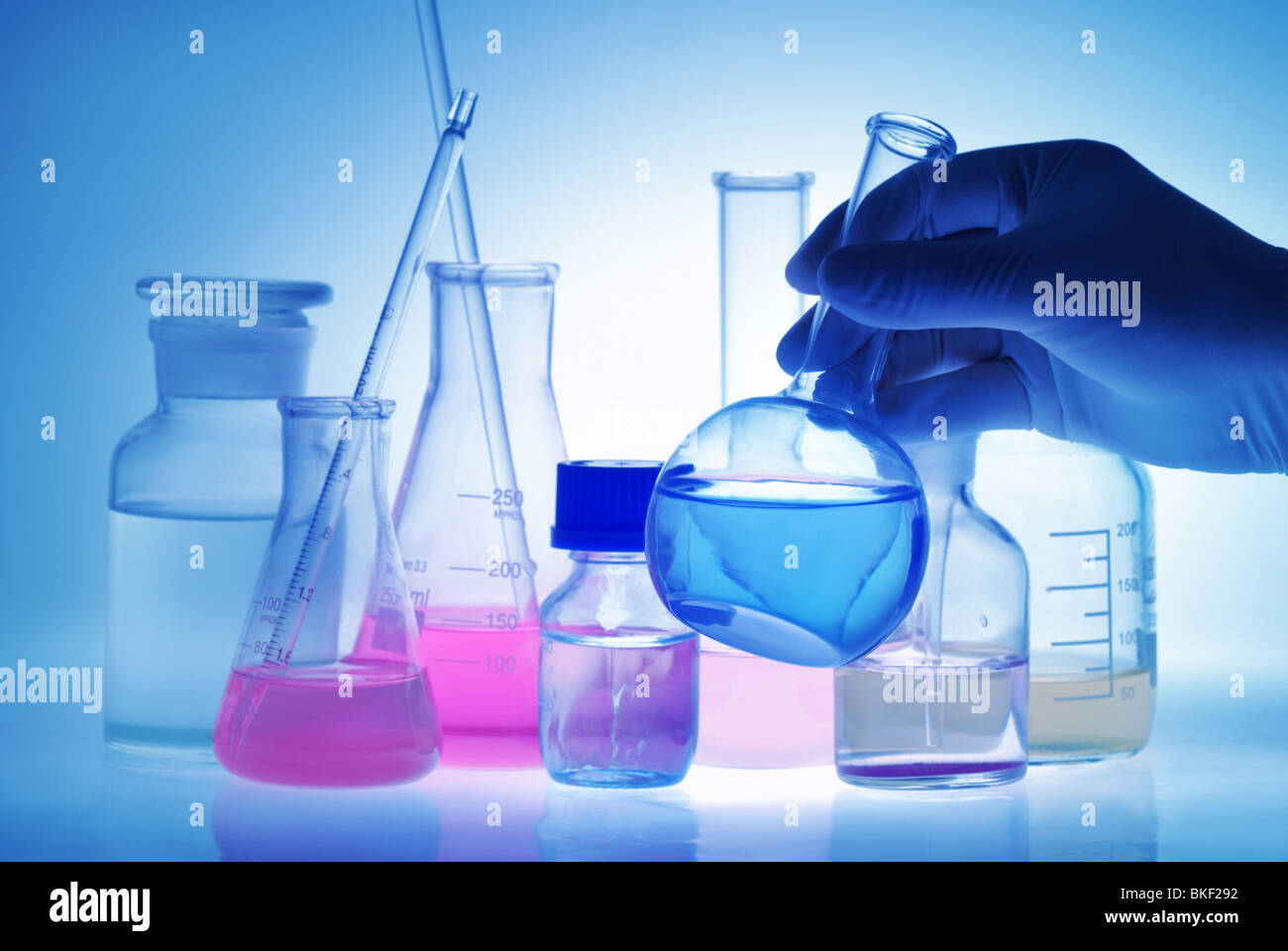 Scientific (or Medical) Experiment--Scientist holding flask in front experiment bottles. - Stock Image