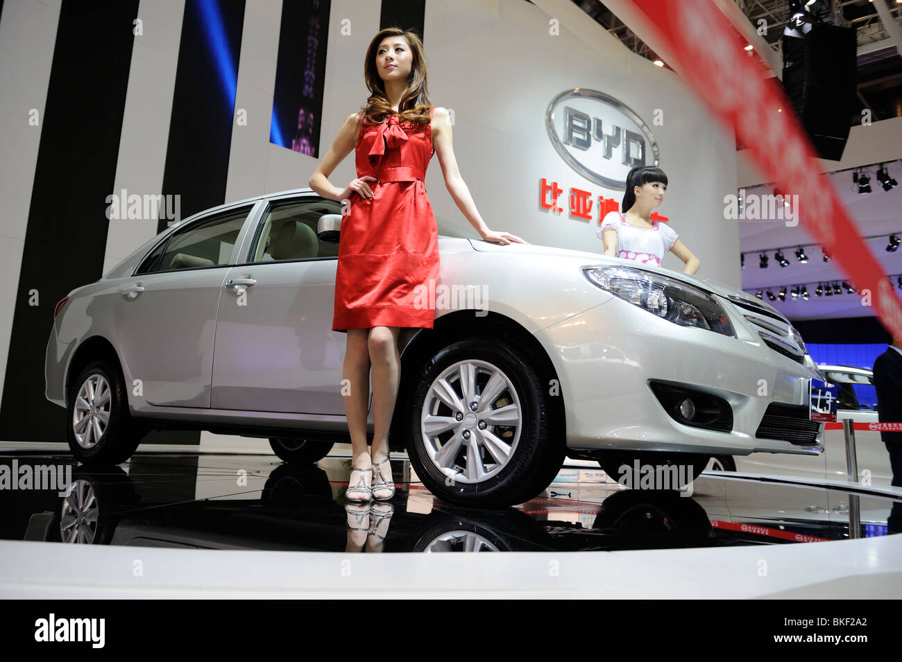 Models pose next BYD L3 sedan at the Beijing Auto Show. 24-Apr-2010 Stock Photo