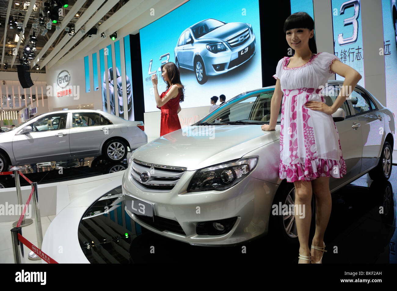 Models pose next BYD L3 sedan at the Beijing Auto Show. 24-Apr-2010 - Stock Image