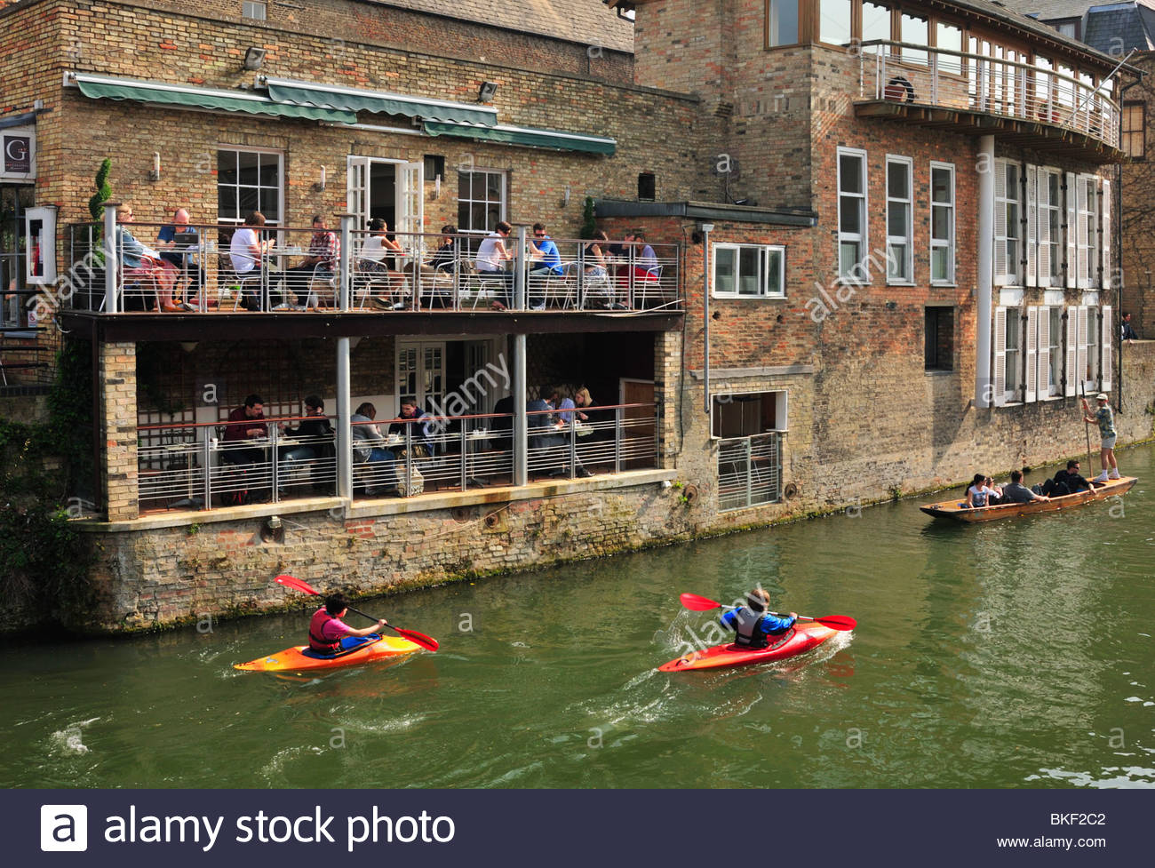 People in riverside Bar watching Punters and Canoeists on the River Cam, Cambridge - Stock Image