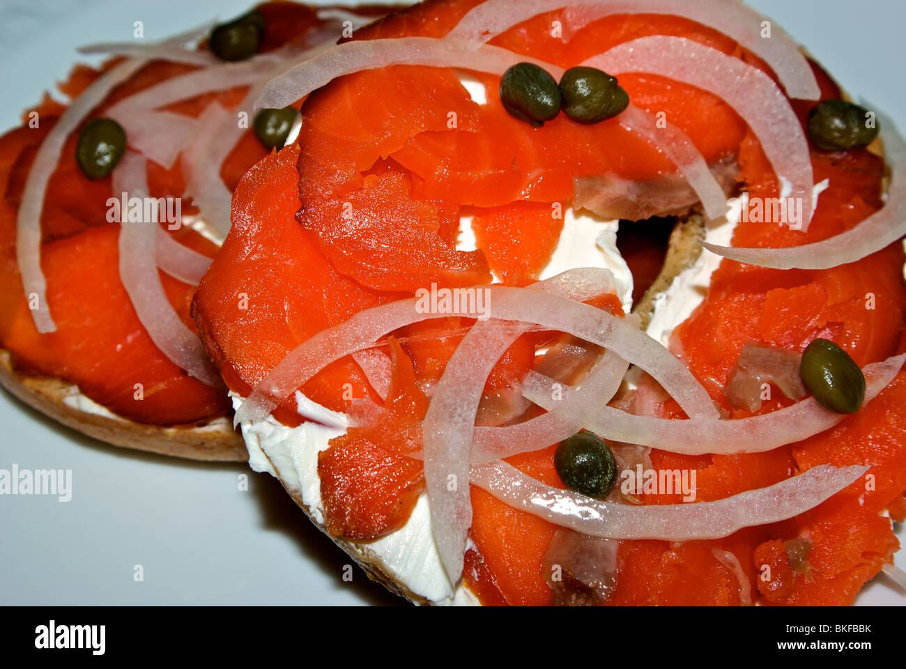 Lox smoked wild red Chinook salmon on healthy whole grain bagel luncheon sandwich with cream cheese thin sliced - Stock Image