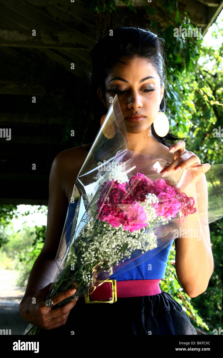 Portrait of a beautiful looking South Asian American woman holding flowers. - Stock Image