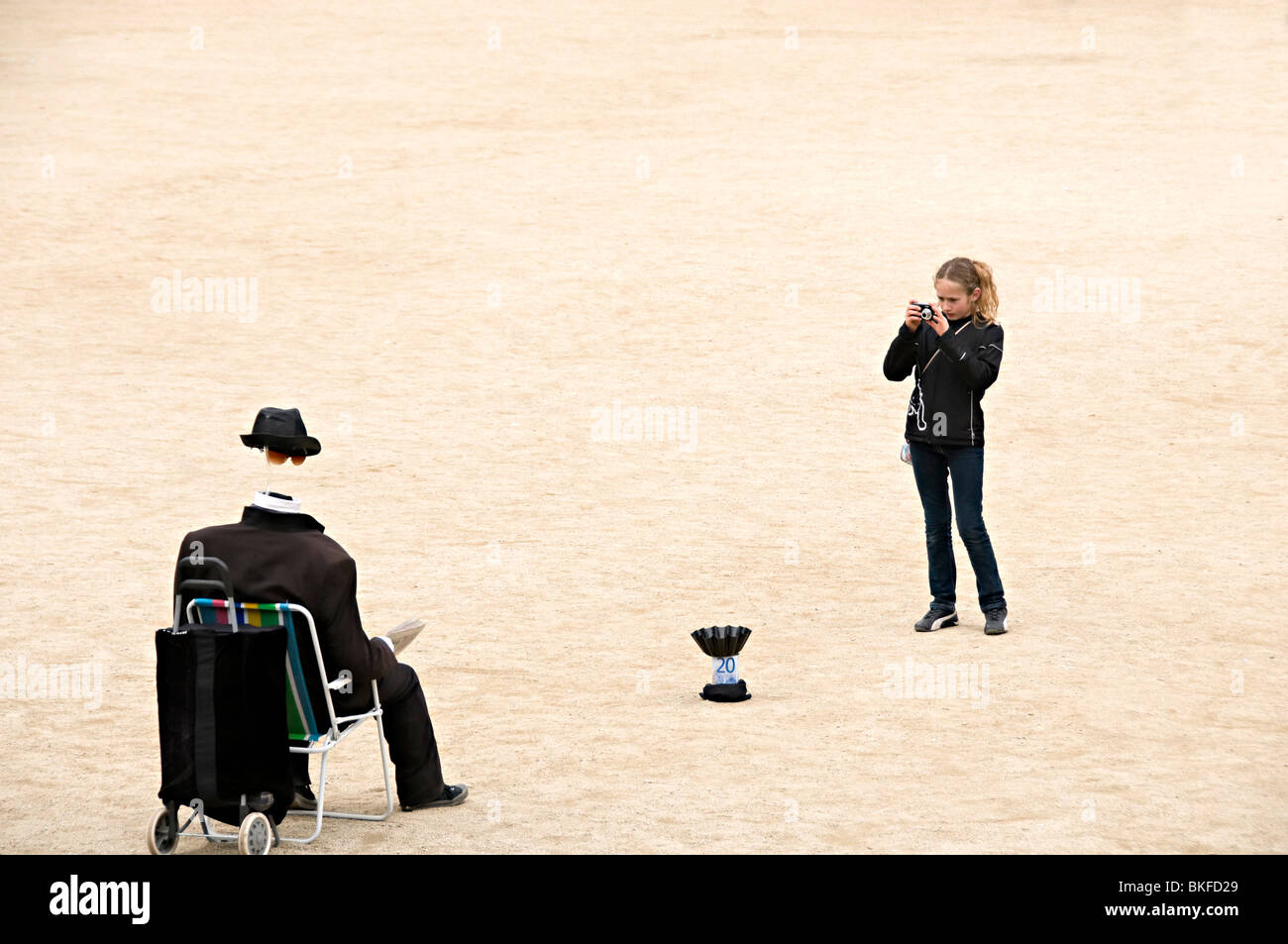 street performer in park guell Barcelona as an invisible man being photographed by a young girl - Stock Image