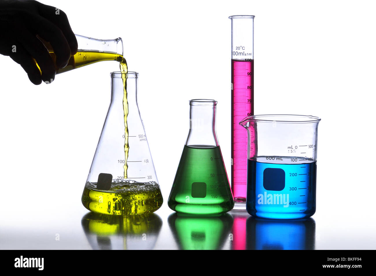 Laboratory Glassware containing different colored liquids against a neutral background - Stock Image
