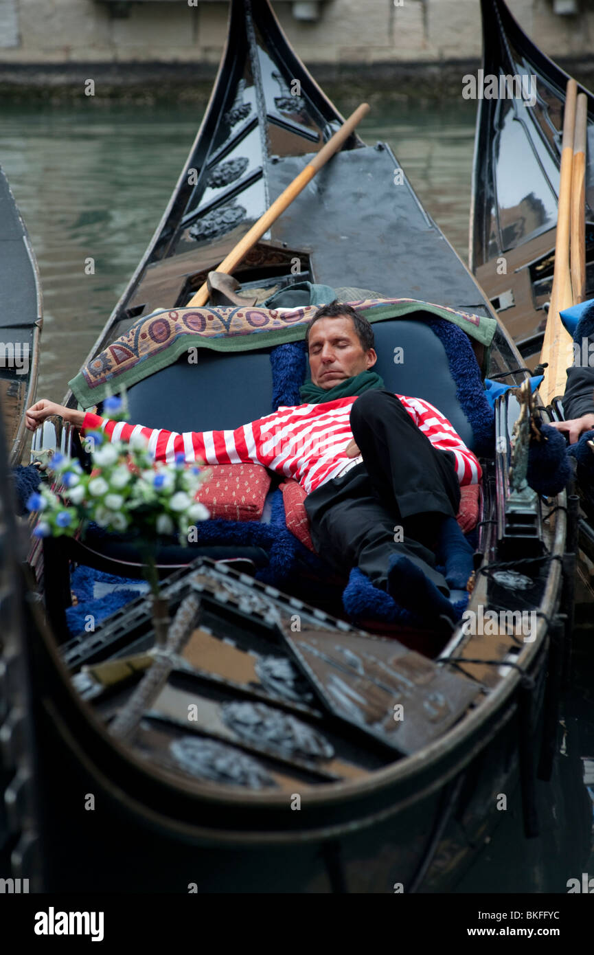 Gondolier sleeping in his gondola on canal in Venice Italy - Stock Image