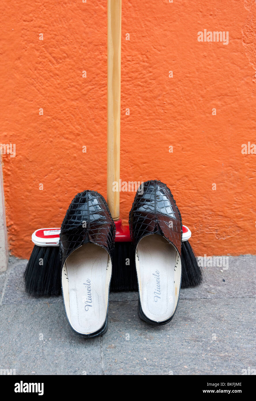 Detail of shoes resting on broom outside colourful orange house in Burano near Venice Italy - Stock Image