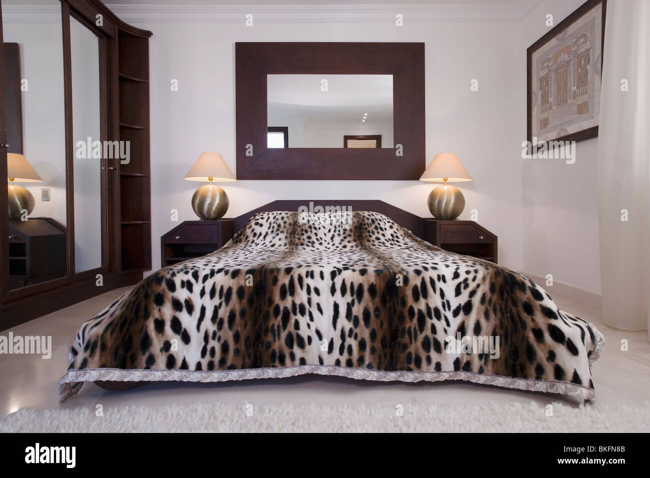 Large Mirror Above Bed With Faux Leopardskin Bed Cover In Modern Bedroom  With Lighted Lamps On Bedside Tables