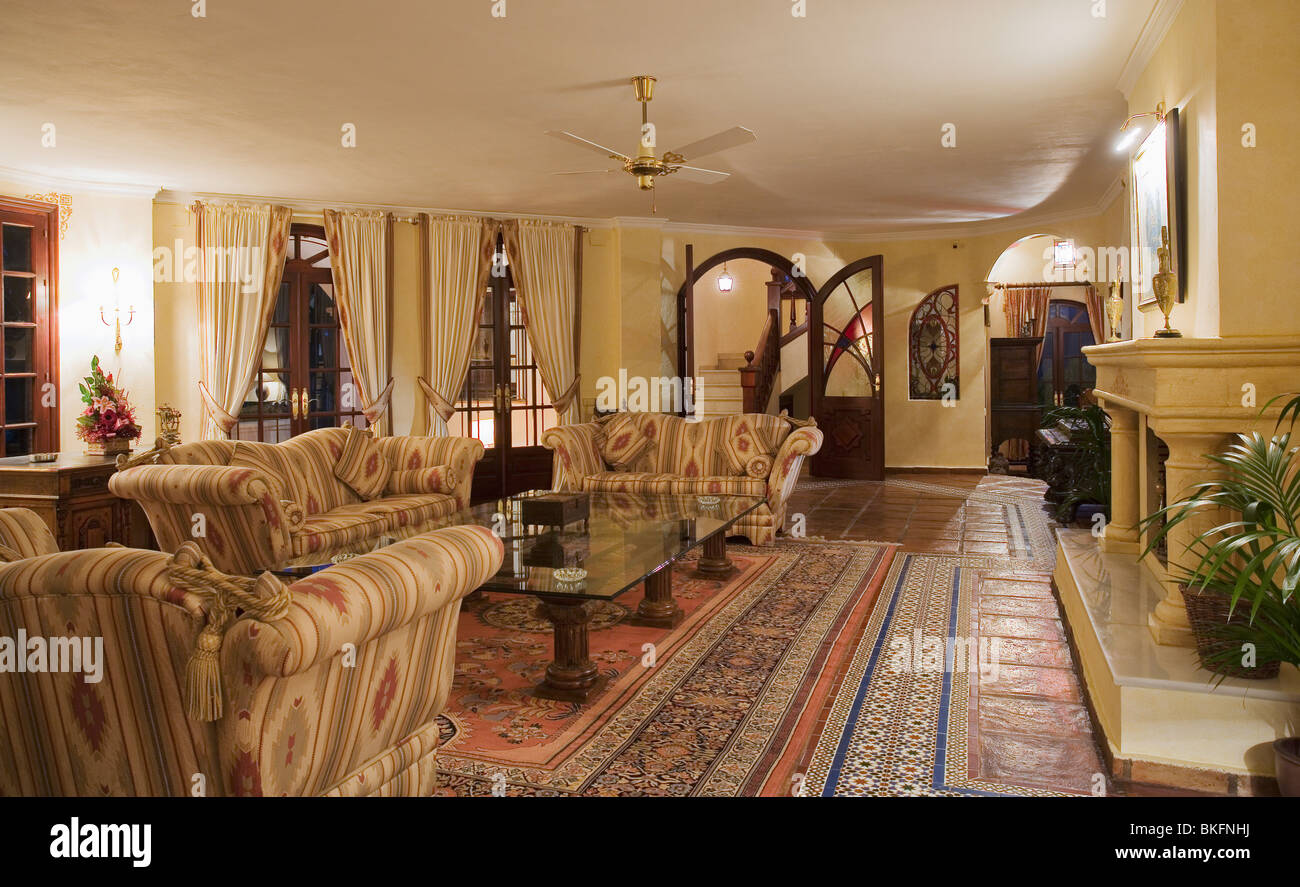 Large patterned sofas in spanish country living room with terracotta and spanish tiled floor