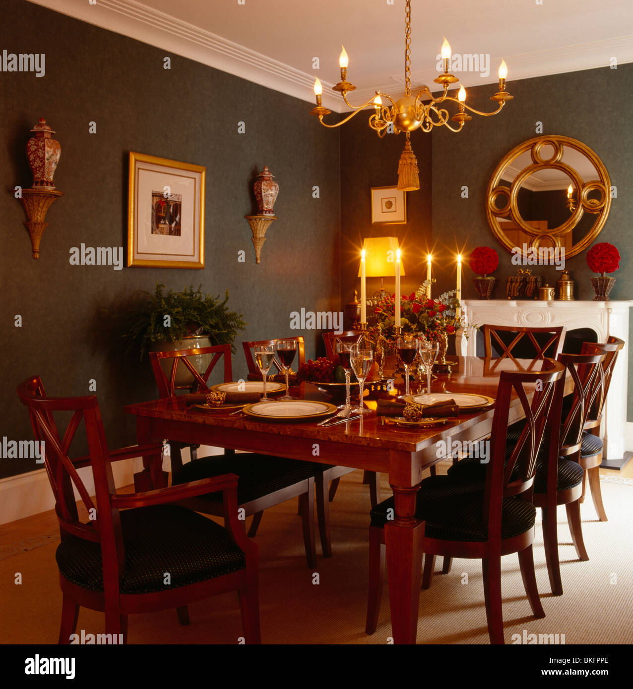 Lighted gilt chandelier above antique table and chairs in ...