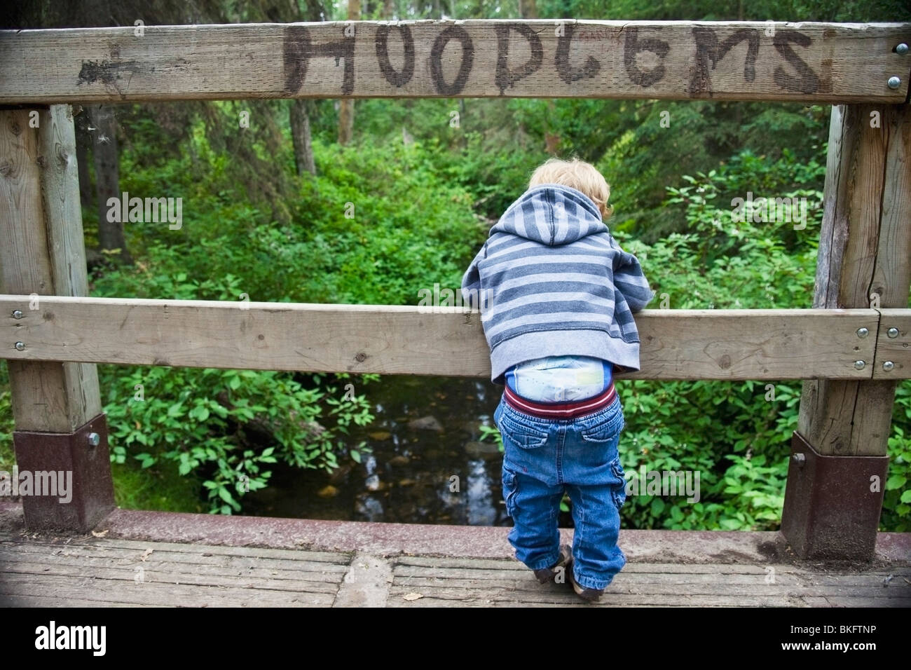 Young Boy Looking Over A Bridge With His Pants Falling Down And The Sign 'Hoodlums' Over His Head - Stock Image