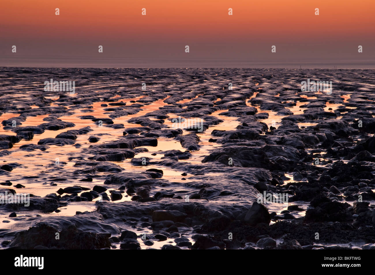 Sunset over the mudflats at Sandpoint, near Weston Super Mare, England - Stock Image