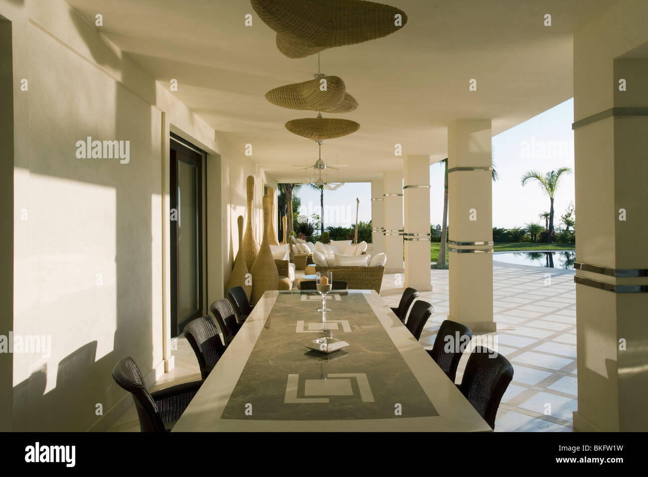 Long Marble Table In Dining And Living Area On Veranda Of Large Spanish  Villa With View Of Swimming Pool