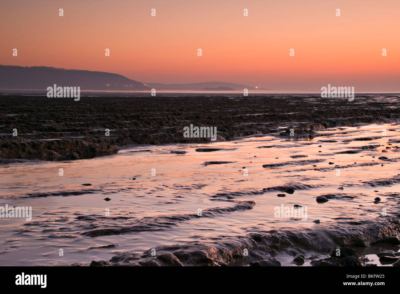 Sunset over the mudflats at Sandpoint, near Weston Super Mare, England with the lights at Weston just visible in - Stock Image