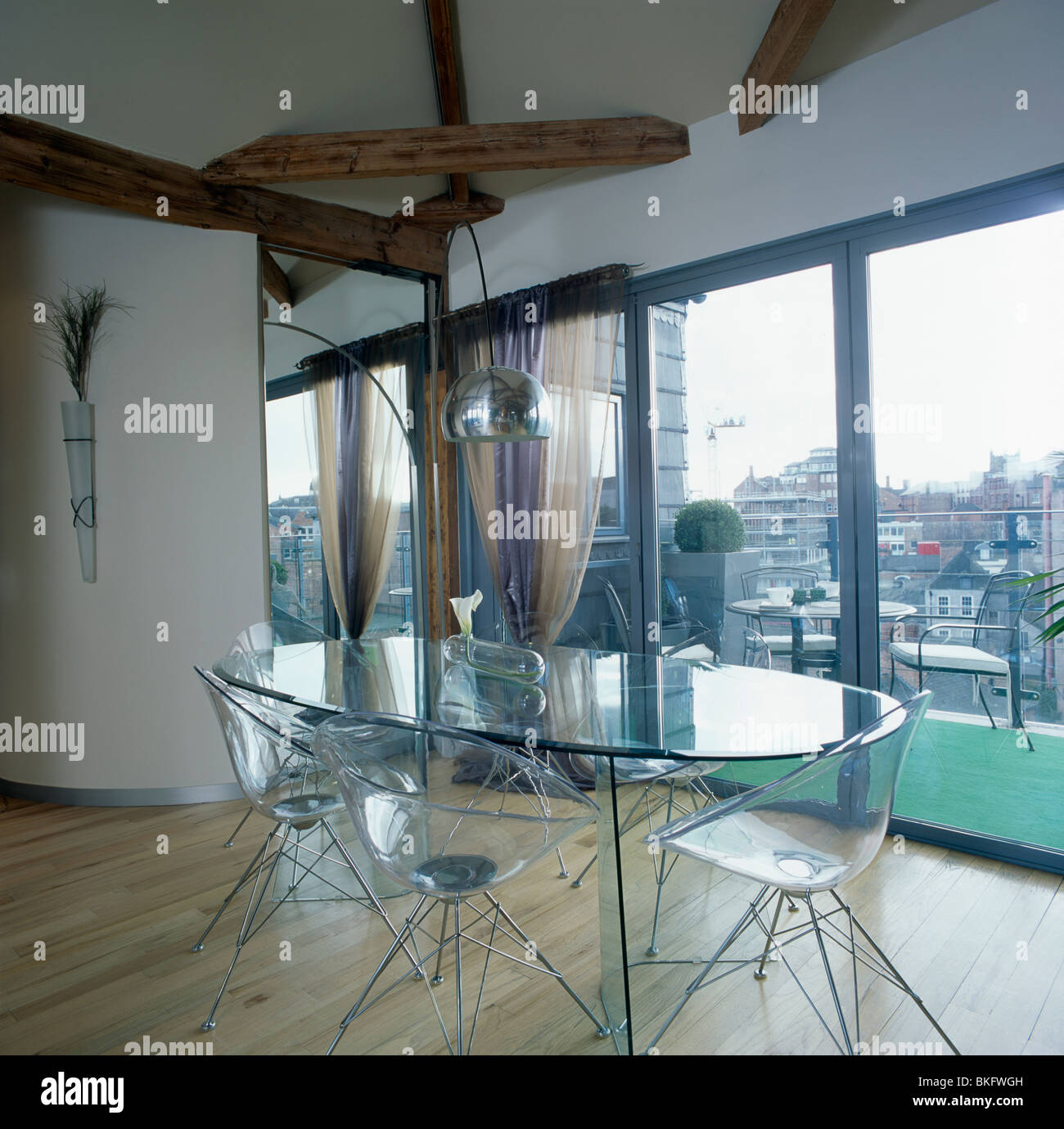 Oval Glass Table And Perspex Chairs In Modern Loft Conversion Dining Room  With Glass Doors With View Of The City