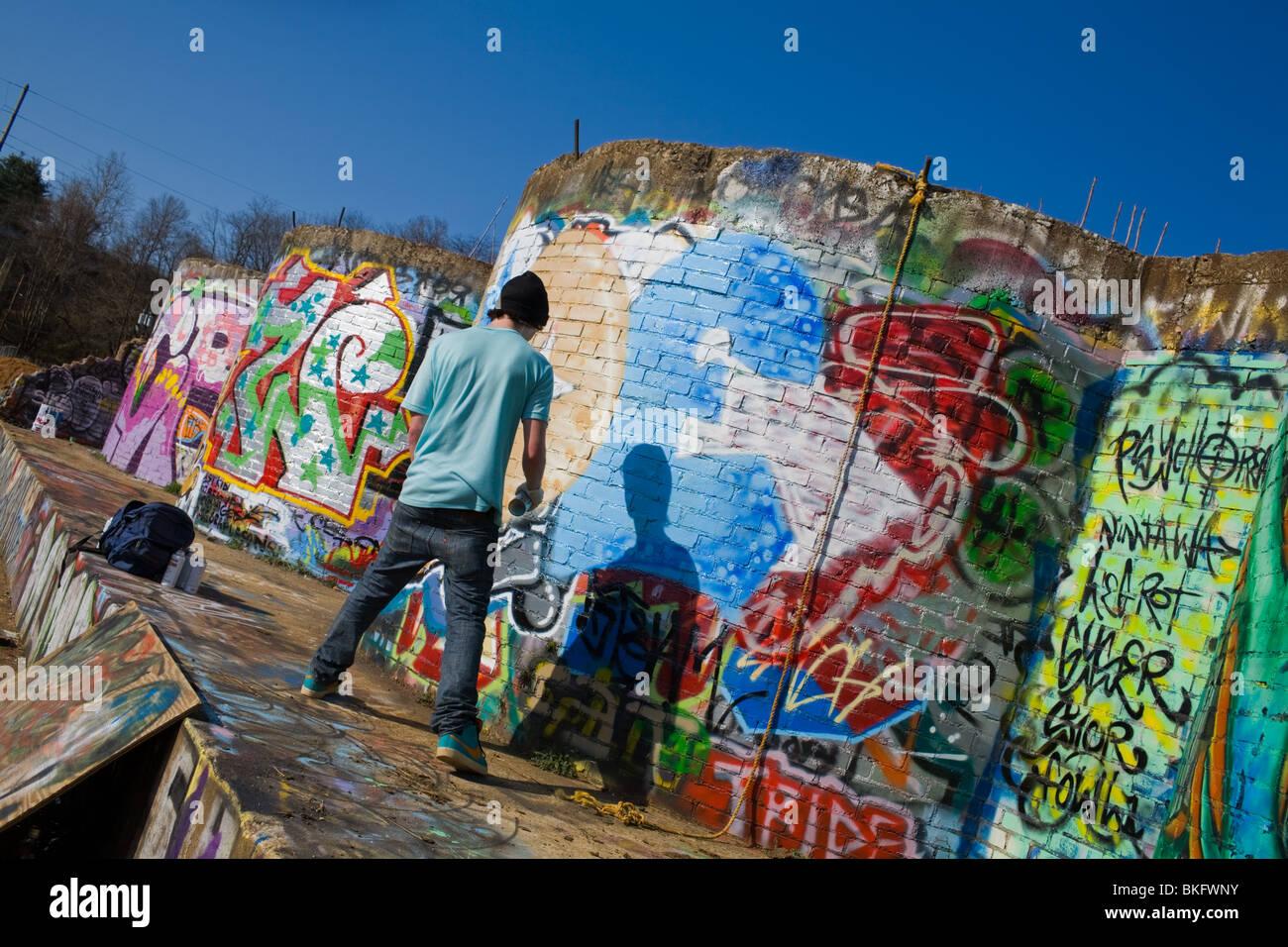 Graffiti artist tagging near railroad tracks, River Arts District, Asheville, North Carolina - Stock Image
