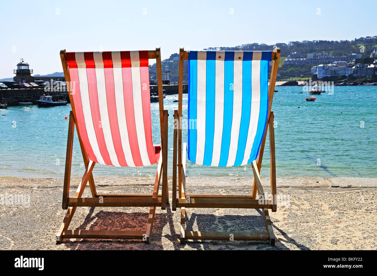 two deck chairs overlooking the harbour at st.ives in cornwall, uk - Stock Image