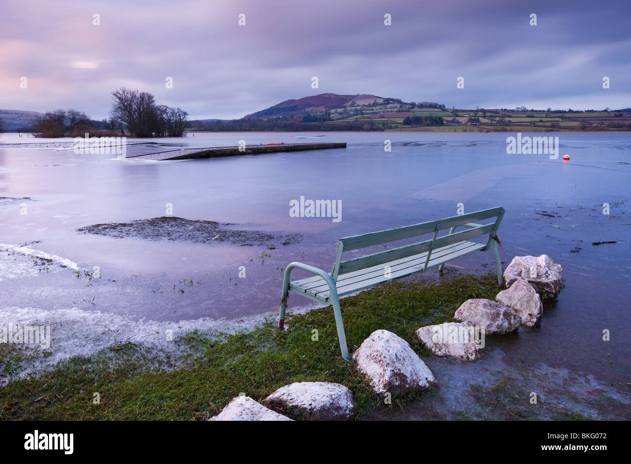 Empty bench on the frozen shores of Llangorse Lake in the Brecon Beacons National Park, Powys, Wales, UK. Winter - Stock Image