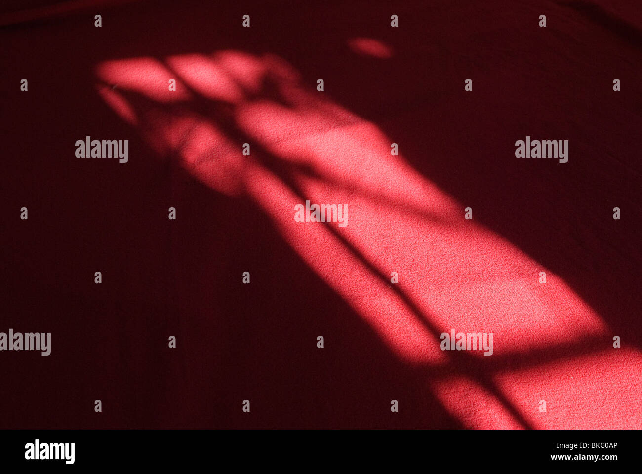 Interior bedroom detail. Pattern from light through curtain windows onto red bedspread. - Stock Image