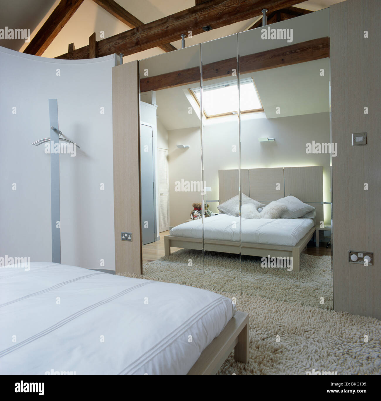Mirrored Wall Tiles Opposite Bed With White Linen In Modern White Stock Photo Alamy
